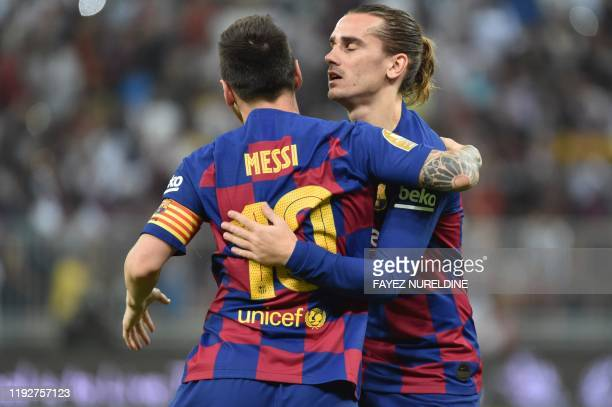 Barcelona's Argentine forward Lionel Messi celebrates with Barcelona's French forward Antoine Griezmann during the Spanish Super Cup semi final...