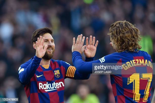 Barcelona's Argentine forward Lionel Messi celebrates with Barcelona's French forward Antoine Griezmann after scoring during the Spanish league...