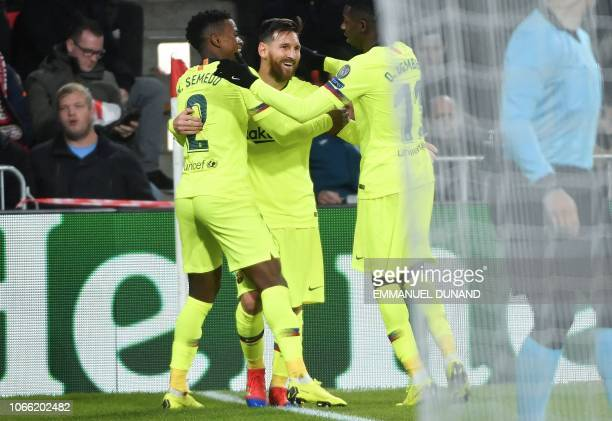 Barcelona's Argentine forward Lionel Messi celebrates with teammates French forward Ousmane Dembele and Portuguese defender Nelson Semedo after...