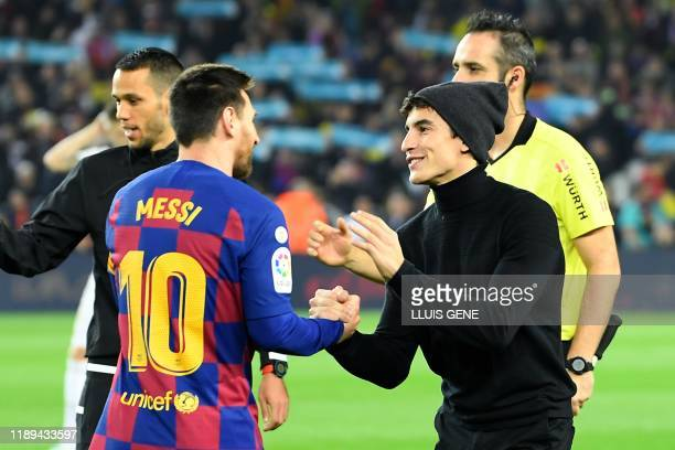 Barcelona's Argentine forward Lionel Messi greets Repsol Honda Team Spanish rider Marc Marquez before the El Clasico Spanish League football match...