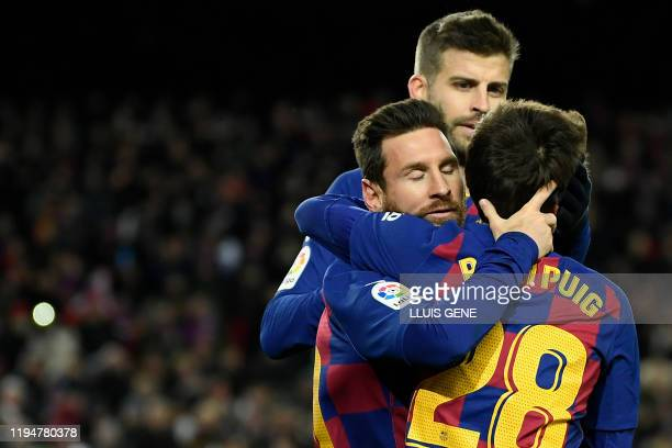 TOPSHOT Barcelona's Argentine forward Lionel Messi is congratulated by Barcelona's Spanish midfielder Riqui Puig after scoring the opening goal...