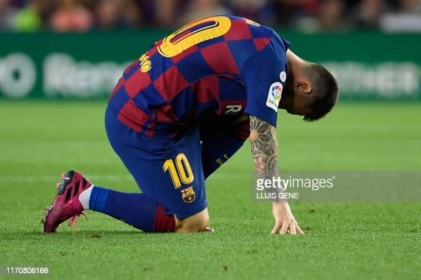 TOPSHOT Barcelona's Argentine forward Lionel Messi reacts on the ground during the Spanish league football match between FC Barcelona and Villarreal...