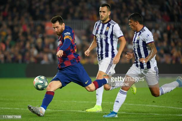Barcelona's Argentine forward Lionel Messi shoots to score his second goal during the Spanish league football match between FC Barcelona and Real...