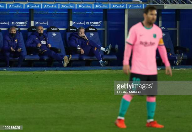 Barcelona's Argentine forward Lionel Messi stands on the pitch as Barcelona's Dutch coach Ronald Koeman sits on the bench during the Spanish League...