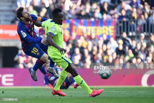 Barcelona's Argentine forward Lionel Messi vies for the ball with Getafe's Togolese defender Djene during the Spanish league football match between...