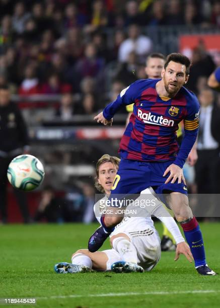 Barcelona's Argentine forward Lionel Messi vies with Real Madrid's Croatian midfielder Luka Modric during the El Clasico Spanish League football...
