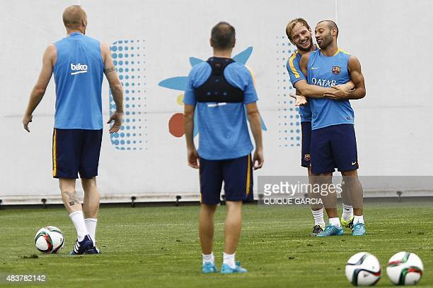 Barcelona's Argentinian defender Javier Mascherano and Barcelona's Croatian midfielder Ivan Rakitic take part in a training session at the Sports...