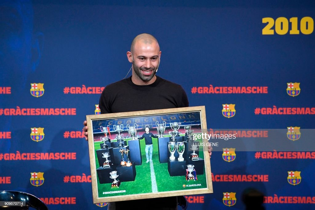 TOPSHOT - Barcelona's Argentinian defender Javier Mascherano poses with a framed picture of him and the major trophies he won with the football club during a farewell ceremony in Barcelona ahead of his transfer to China on January 24, 2018. Mascherano was unveiled as the latest big name to move to China, signing for Hebei China Fortune from Barcelona. /