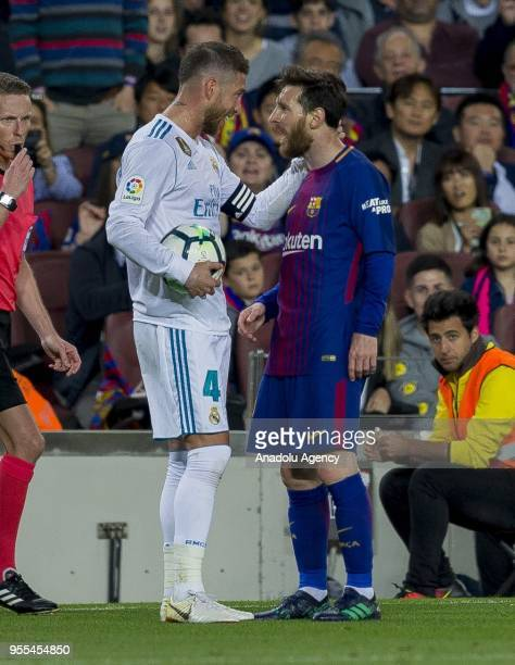 Barcelona's Argentinian forward Leo Messi talks to Real Madrid defender Sergio Ramos during the Spanish league football match between FC Barcelona...