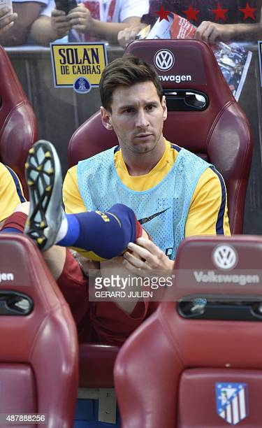 Barcelona's Argentinian forward Lionel Messi adjusts his sock as he sits on the bench prior to the Spanish league football match Club Atletico de...