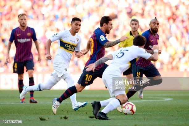 TOPSHOT Barcelona's Argentinian forward Lionel Messi advances with the ball past Boca Juniors' Uruguayan midfielder Nahitan Nandez and Boca Juniors'...