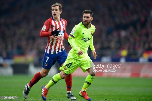 Barcelona's Argentinian forward Lionel Messi and Atletico Madrid's French forward Antoine Griezmann wait to be passed the ball during the Spanish...