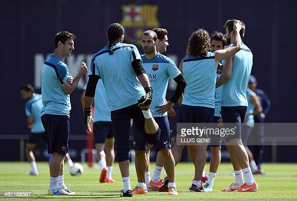 Barcelona's Argentinian forward Lionel Messi and Barcelona's Argentinian midfielder Javier Mascherano chat during a training session at the Sports...