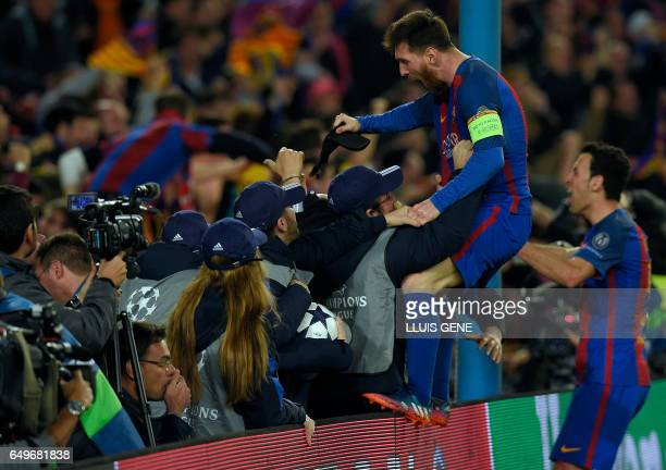 Barcelona's Argentinian forward Lionel Messi and Barcelona's midfielder Sergio Busquets celebrate their victory at the end of the UEFA Champions...