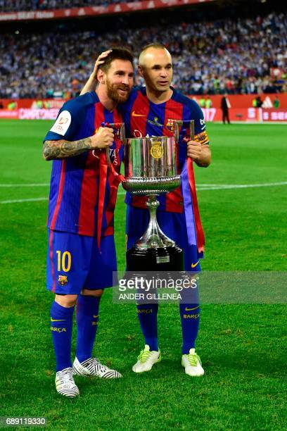 Barcelona's Argentinian forward Lionel Messi and Barcelona's midfielder Andres Iniesta hold up the trophy after the team won the Spanish Copa del Rey...
