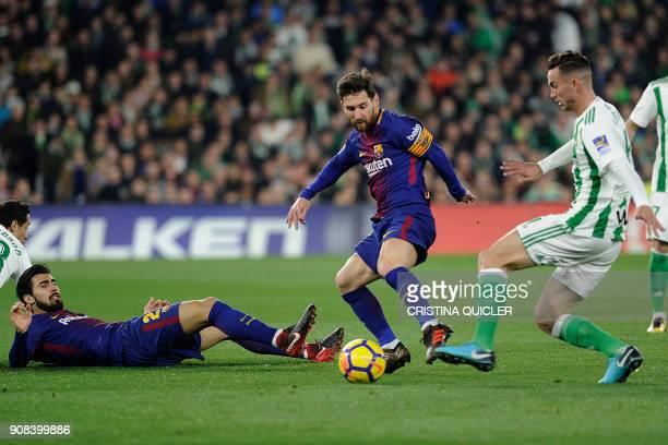 Barcelona's Argentinian forward Lionel Messi and Barcelona's Portuguese midfielder Andre Gomes challenge Real Betis' Spanish midfielder Fabian Ruiz...