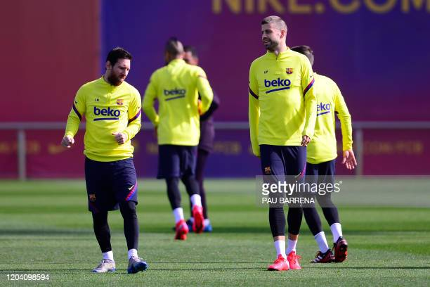 Barcelona's Argentinian forward Lionel Messi and Barcelona's Spanish defender Gerard Pique attend a training session at the Joan Gamper training...