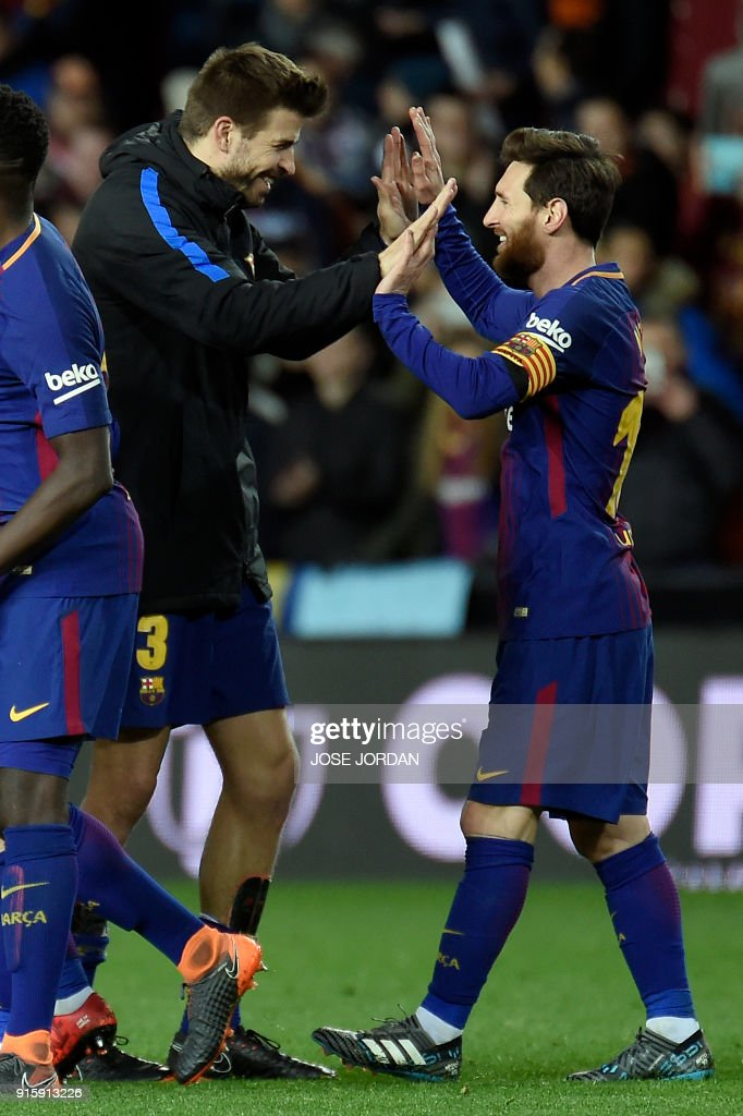 Barcelona's Argentinian forward Lionel Messi (R) and Barcelona's Spanish defender Gerard Pique celebrate their qualification for the final match during the Spanish 'Copa del Rey' (King's cup) second leg semi-final football match between Valencia CF and FC Barcelona at the Mestalla stadium in Valencia on February 8, 2018. /
