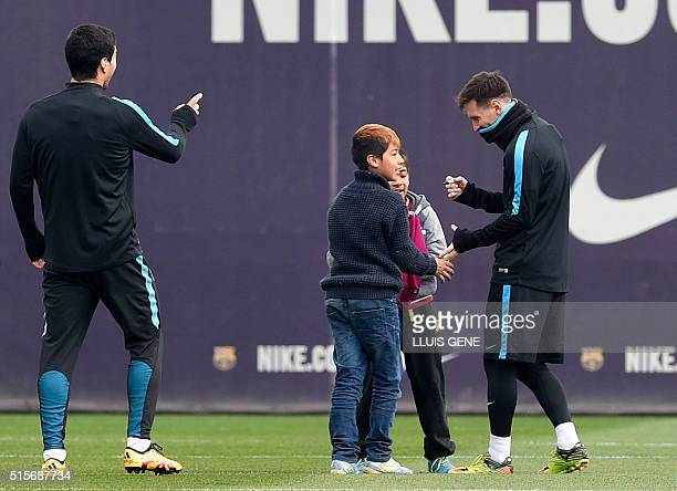 Barcelona's Argentinian forward Lionel Messi and Barcelona's Uruguayan forward Luis Suarez sign autographs for children who gate-crashed the training...