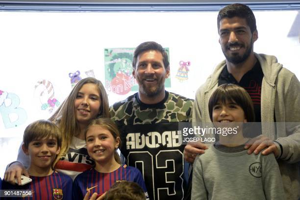 Barcelona's Argentinian forward Lionel Messi and Barcelona's Uruguayan forward Luis Suarez meet with children at the Sant Pau Hospital in Barcelona...
