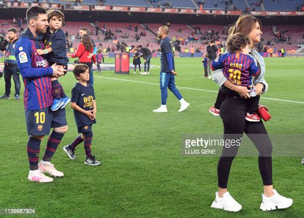 Barcelona's Argentinian forward Lionel Messi and his wife Antonella Roccuzzo walk on the pitch with their children as they celebrate becoming La Liga...