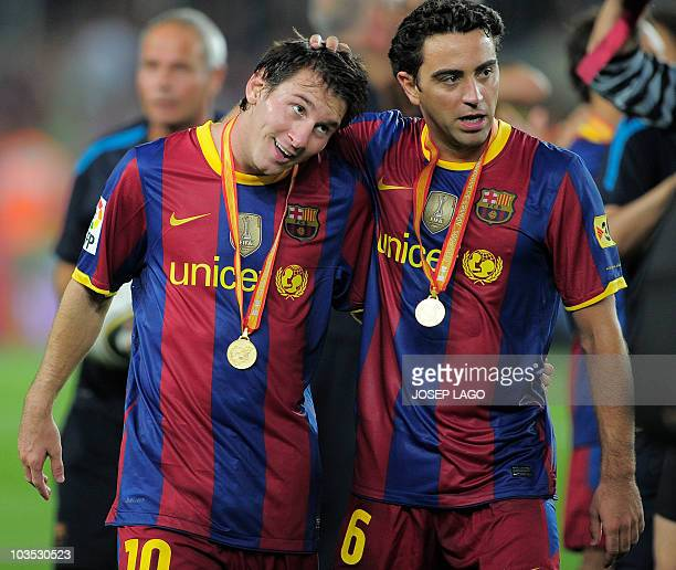 Barcelona's Argentinian forward Lionel Messi and midfielder Xavi Hernandez celebrate their Spanish Supercup title after beating the Sevilla team at...