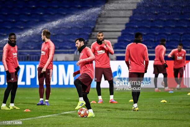 Barcelona's Argentinian forward Lionel Messi and other Barcelona's players take part in a training session at the Parc Olympique Lyonnais stadium in...