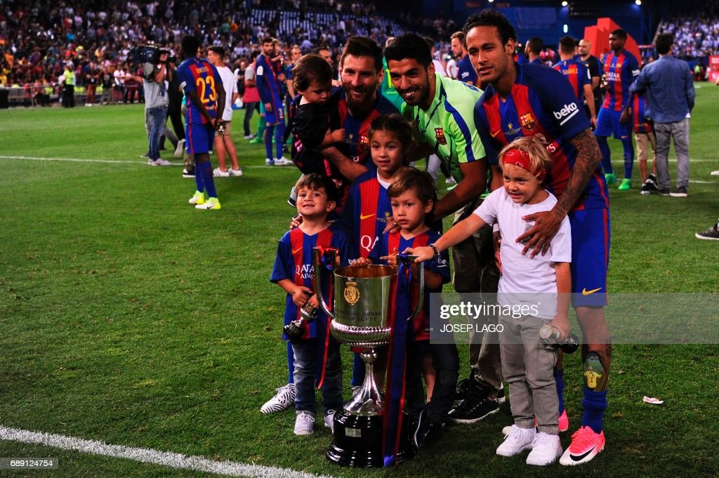 Barcelona's Argentinian forward Lionel Messi, Barcelona's Uruguayan forward Luis Suarez, Barcelona's Brazilian forward Neymar and their kids pose with the trophy at the end of the Spanish Copa del Rey (King's Cup) final football match FC Barcelona vs Deportivo Alaves at the Vicente Calderon stadium in Madrid on May 27, 2017. Barcelona won 3-1. / AFP PHOTO / Josep LAGO