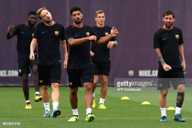 Barcelona's Argentinian forward Lionel Messi Barcelona's Uruguayan forward Luis Suarez and Barcelona's Croatian midfielder Ivan Rakitic take part in...