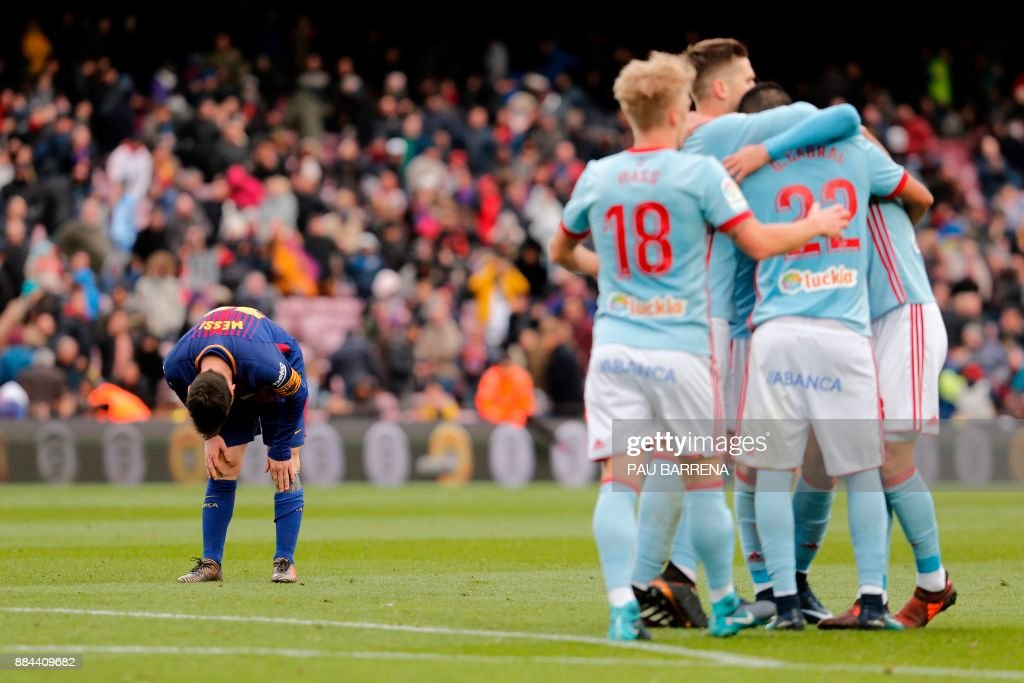 TOPSHOT - Barcelona's Argentinian forward Lionel Messi (L) bends at the end of the Spanish league football match FC Barcelona vs RC Celta at the Camp Nou stadium in Barcelona on December 2, 2017. /