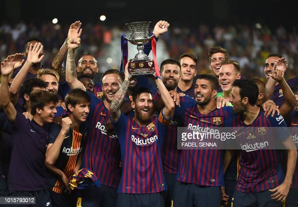 Barcelona's Argentinian forward Lionel Messi carries the cup as they celebrate at the end of the Spanish Super Cup final between Sevilla FC and FC...