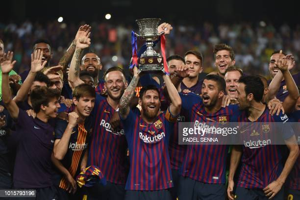 TOPSHOT Barcelona's Argentinian forward Lionel Messi carries the cup as they celebrate at the end of the Spanish Super Cup final between Sevilla FC...