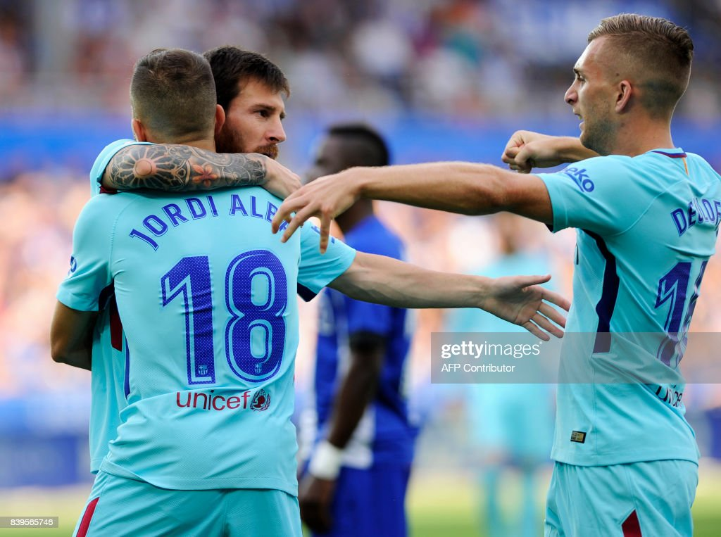 Barcelona's Argentinian forward Lionel Messi (2ndL) celebartes with defender Jordi Alba (L) and forward Gerard Deulofeu (R) after scoring during the Spanish league football match Deportivo Alaves vs FC Barcelona at the Memorandize stadium in Vitoria on August 26, 2017. /
