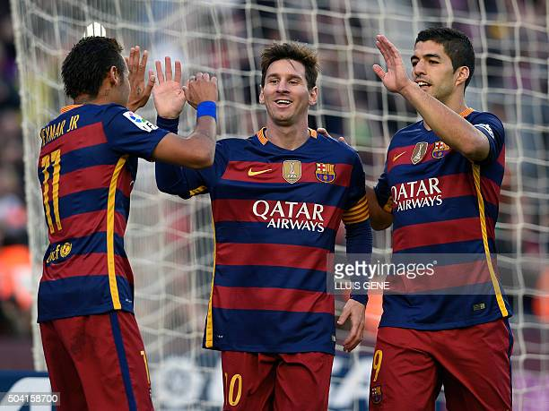 Barcelona's Argentinian forward Lionel Messi celebrates a goal with Barcelona's Brazilian forward Neymar and Barcelona's Uruguayan forward Luis...