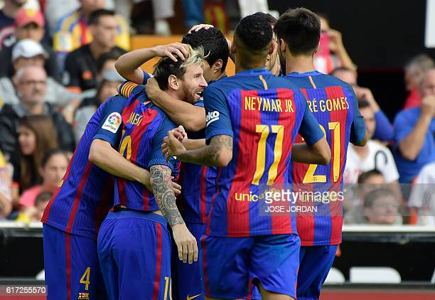 Barcelona's Argentinian forward Lionel Messi celebrates a goal with teammates during the Spanish league football match between Valencia CF and FC...