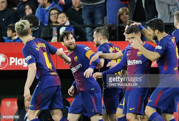 Barcelona's Argentinian forward Lionel Messi celebrates a goal with teammates during the Spanish League football match between Sevilla FC and FC...