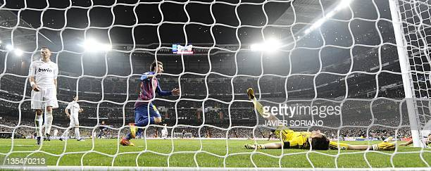 Barcelona's Argentinian forward Lionel Messi celebrates after Barcelona's midfielder Cesc Fabregas scored Barcelona's third goal next to Real...