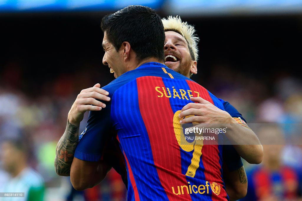 TOPSHOT - Barcelona's Argentinian forward Lionel Messi (R) celebrates after scoring with Barcelona's Uruguayan forward Luis Suarez during the Spanish league football match FC Barcelona vs Real Betis Balompie at the Camp Nou stadium in Barcelona on August 20, 2016. / AFP / PAU