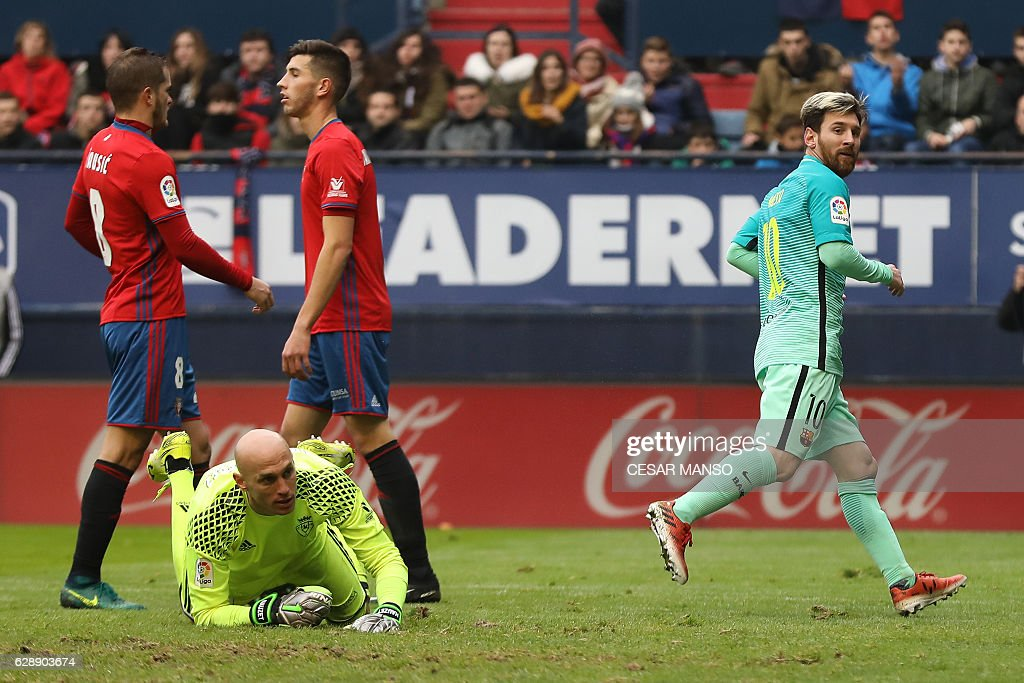Barcelona's Argentinian forward Lionel Messi (R) celebrates after scoring during the Spanish league football match CA Osasuna vs FC Barcelona at the Reyno de Navarra (El Sadar) stadium in Pamplona on December 10, 2016. / AFP / CESAR
