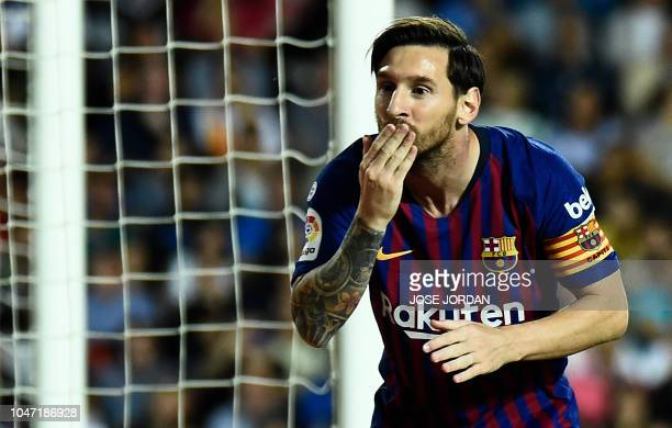 TOPSHOT Barcelona's Argentinian forward Lionel Messi celebrates scoring a goal during the Spanish league football match between Valencia CF and FC...