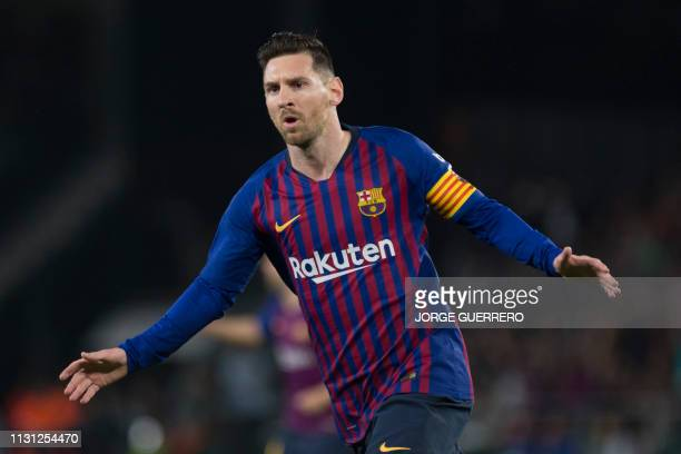 Barcelona's Argentinian forward Lionel Messi celebrates scoring the opening goal during the Spanish league football match between Real Betis and FC...