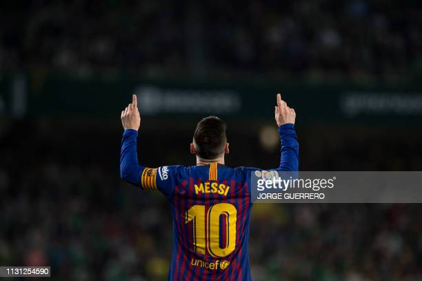 TOPSHOT Barcelona's Argentinian forward Lionel Messi celebrates scoring the opening goal during the Spanish league football match between Real Betis...