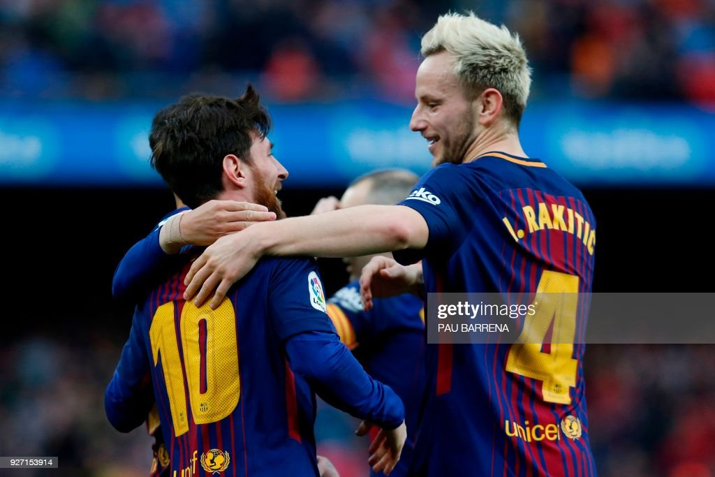 Barcelona's Argentinian forward Lionel Messi (L) celebrates with Barcelona's Croatian midfielder Ivan Rakitic after scoring during the Spanish league football match FC Barcelona against Club Atletico de Madrid at the Camp Nou stadium in Barcelona on March 04, 2018. / AFP PHOTO / Pau Barrena
