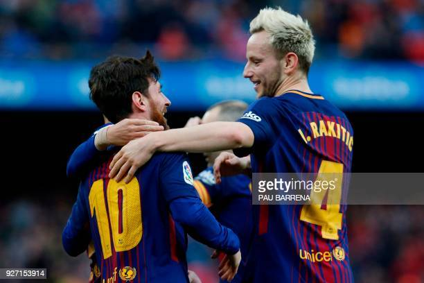 Barcelona's Argentinian forward Lionel Messi celebrates with Barcelona's Croatian midfielder Ivan Rakitic after scoring during the Spanish league...