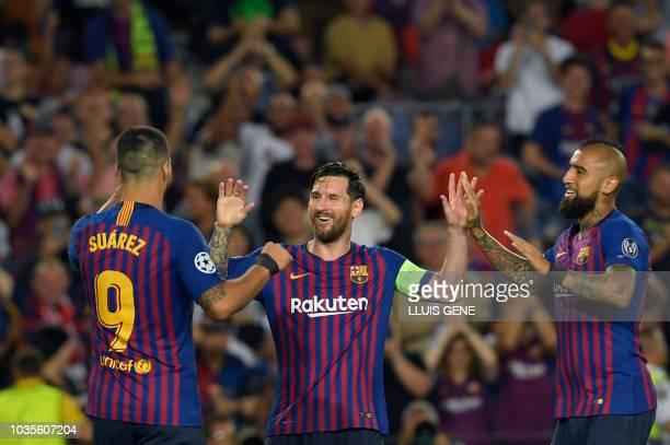 Barcelona's Argentinian forward Lionel Messi celebrates with Barcelona's Uruguayan forward Luis Suarez and Barcelona's Chilean midfielder Arturo...