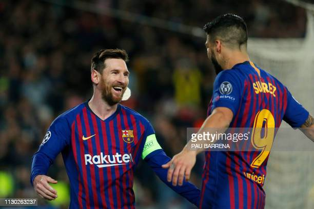 Barcelona's Argentinian forward Lionel Messi celebrates with Barcelona's Uruguayan forward Luis Suarez after scoring during the UEFA Champions League...