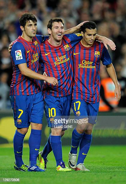 Barcelona's Argentinian forward Lionel Messi celebrates with Barcelona's forward David Villa and Barcelona's forward Pedro Rodriguez after scoring...