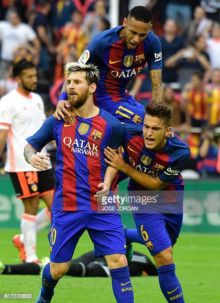 Barcelona's Argentinian forward Lionel Messi celebrates with Barcelona's Brazilian forward Neymar and Barcelona's midfielder Denis Suarez after...