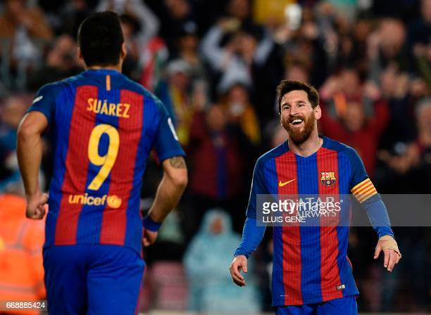 Barcelona's Argentinian forward Lionel Messi celebrates with Barcelona's Uruguayan forward Luis Suarez after scoring a goal during the Spanish league...