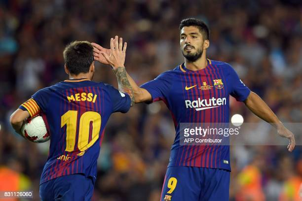 Barcelona's Argentinian forward Lionel Messi celebrates with Barcelona's Uruguayan forward Luis Suarez after scoring a goal following a penalty kick...